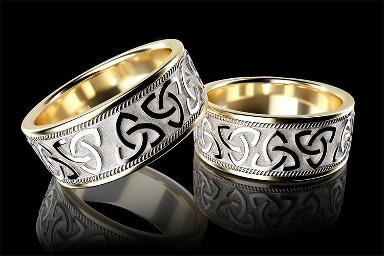Br24 Blog Retouching CGI vs. Photography: CGI, two shiny silver and golden finger rings with ornate pattern in front of black background, reflections below