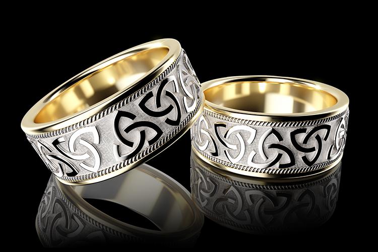 Br24 Blog Retusche von CGI vs. Fotografie: CGI, zwei glänzende silberne und goldene Fingerringe mit aufwändigem Muster vor schwarzem Hintergrund, Reflexionen unten