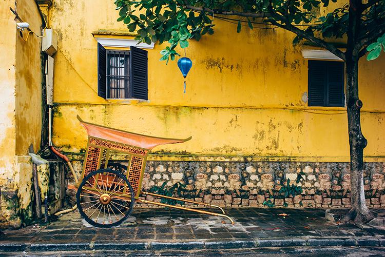 Br24 Blog Retusche von CGI vs. Fotografie: Fotografie, Straßenszene, kleine asiatische Kutsche draußen vor gelber Hauswand