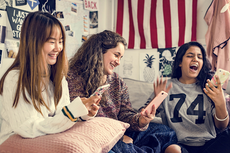 Br24 Blog Visual Trends 2019 - Creative Democracy: Three young women sitting together with smartphones in their hands, laughing and having fun