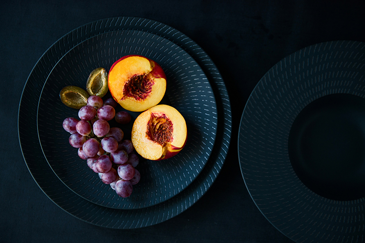 Br24 Food Photography: Dark blue plates on black surface, sliced orange nectarines and violet grapes whose colours stand out from the dark surroundings, photographed from above