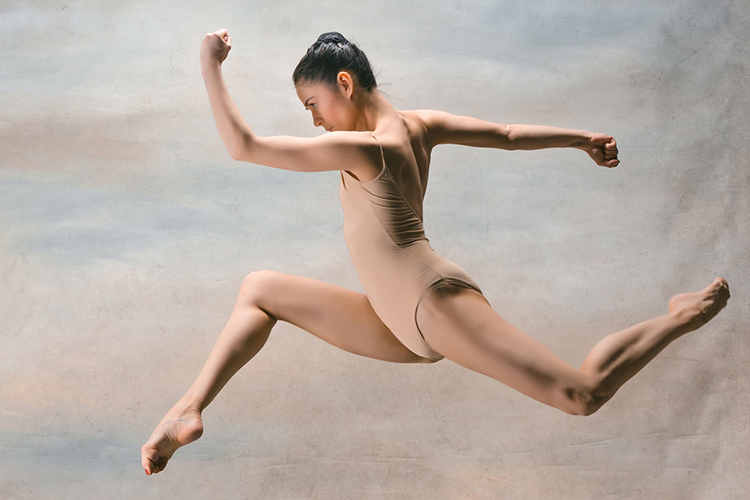Br24 Blog Visual Trends 2019 - Disruptive Expression: Female dancer in dance suit, captured in the middle of a powerful jump from right to left