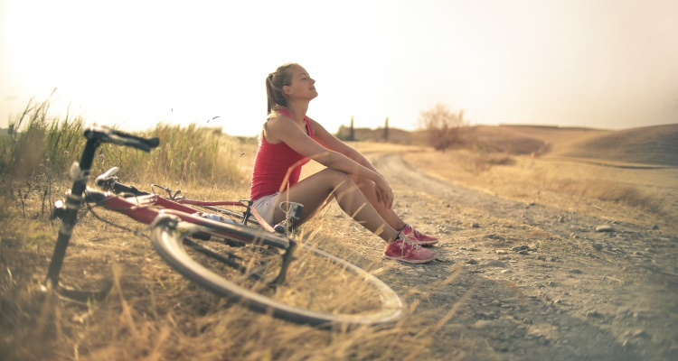 Br24 Blog Adobe Stock's 2021 Creative Trends: Visual Trend Breath of Fresh Air, woman sitting relaxed with her bike on a road outside in the sun