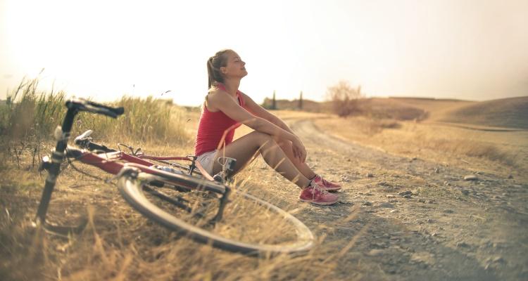 Br24 Blog Adobe Stock Creative Trends 2021: Visual Trend Breath of Fresh Air, Frau sitzt entspannt mit ihrem Fahrrad auf einem Weg draußen in der Sonne