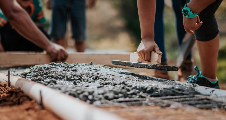 Br24 Blog Adobe Stock Creative Trends 2021: Visual Trend Compassionate Collektive, Detailansicht von Händen, die etwas aus Zement bauen