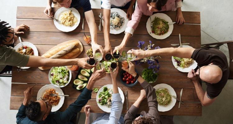 Br24 Blog Adobe Stock Creative Trends 2021: Visual Trend Comfort Zone, Draufsicht auf eine Gruppe von Menschen an einem Tisch, die zusammen trinken und essen
