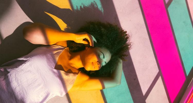 Br24 Blog Adobe Stock Creative Trends 2021: Visual Trend Mood Boosting Colors, Frau die entspannt auf dem Boden in buntem Licht liegt
