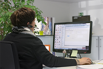 Br24 Team: Woman with headset in front of a computer screen, discussing orders with clients