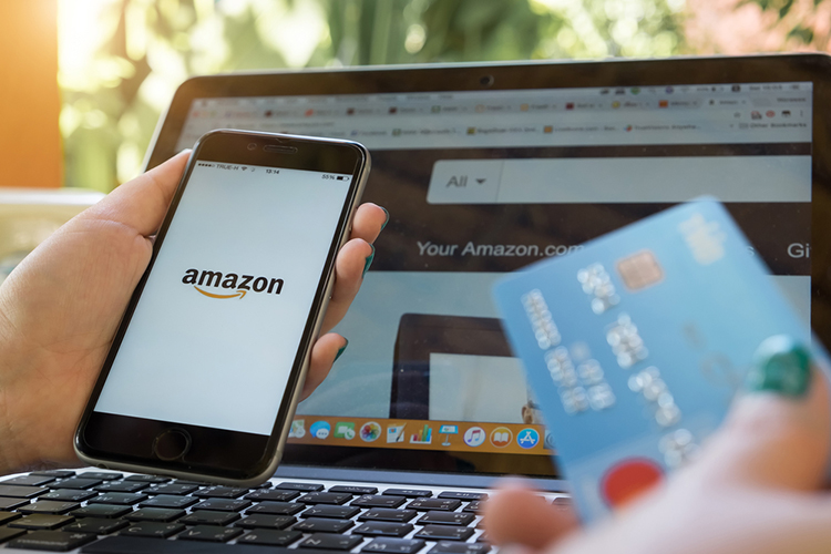 Br24 Blog Wie Amazon die Welt des Handels verändert: Bildschirm von Laptop und Smartphone mit Amazon- Webseite und -Logo, im Vordergrund eine verschwommene Kreditkarte