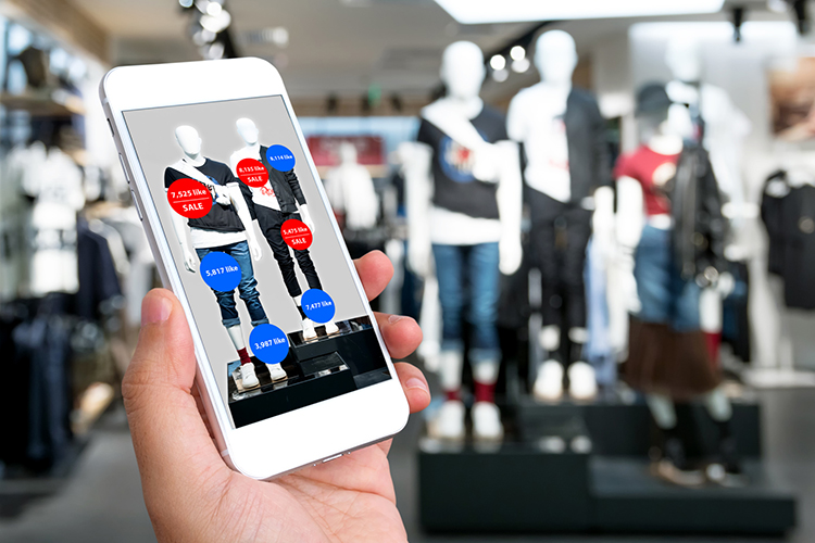 Br24 Blog CGI & Augmented Reality: In the foreground a hand with smartphone, in the background shop with clothes, display of detailed information and offers on the smartphone in real time