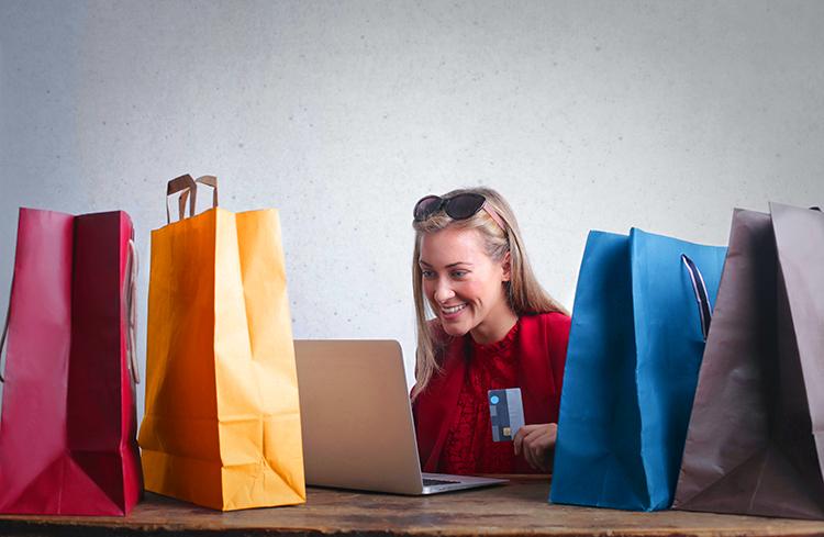 Br24 Blog Vermarktung an Verbraucher zu Hause: Frau mit Kreditkarte vor Laptop umgeben von Einkaufstüten