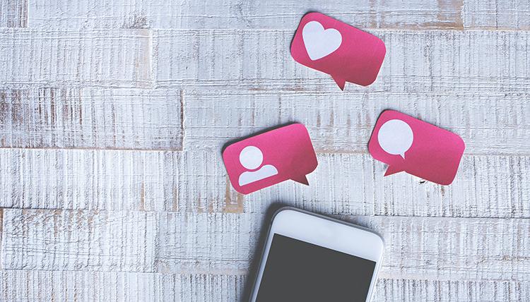 Br24 Blog Vermarktung an Verbraucher zu Hause: Draufsicht auf Smartphone und Post-its mit Social-Media-Symbolen