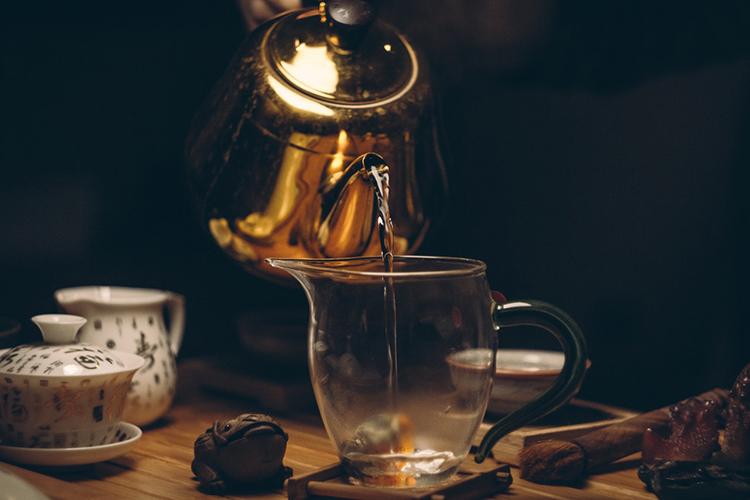 Br24 Blog 7 Photo Editing Styles - Dark & Moody: golden teapot from which tea is poured into a glass cup, dark atmosphere with mood lighting