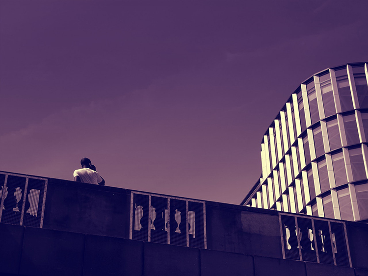 Br24 Blog 7 Photo Editing Styles - Monochrome Style: Person from behind, standing on a bridge near a modern building, photo only in violet tones
