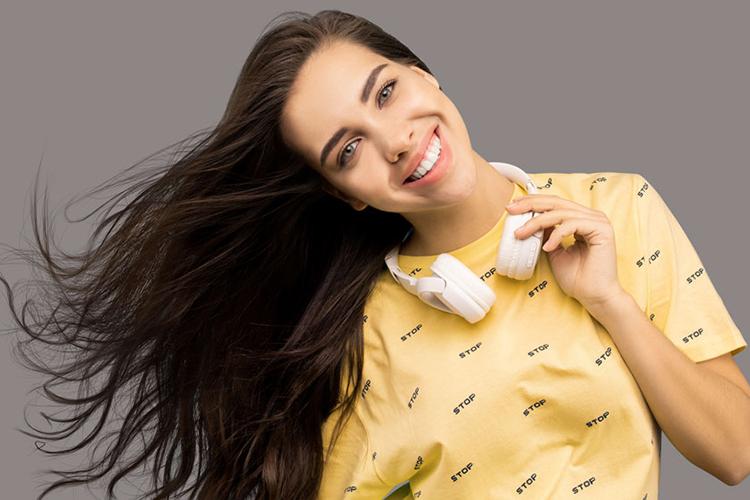 Br24 Blog Der perfekte Hintergrund für Produktfotos: Lächelnde Frauen mit gelbem Hemd und weißen Kopfhörern vor grauem Hintergrund