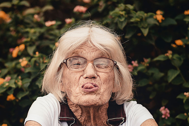 Br24 Blog Visuelle Trends 2020: Trend - All Ages Welcome; Porträt einer glücklichen, älteren Frau die dem Betrachter die Zunge herausstreckt