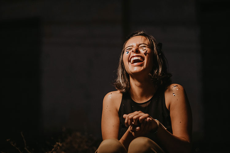 Br24 Blog Visual Trends 2020: Trend - Express Yourself; happily laughing woman with glitter on her face and arms