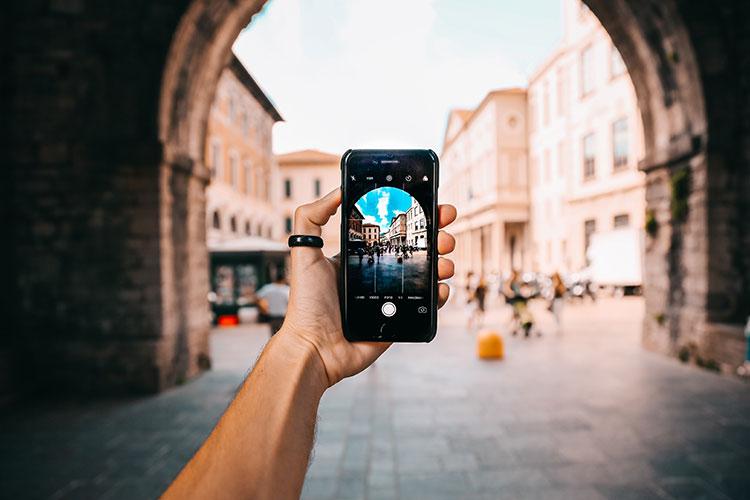 Br24 Blog Visual Trends 2020: Trend - Phoneography; Hand die ein Smartphone hält, Fotomodus auf dem Bildschirm, vor einem unscharfen Hintergrund