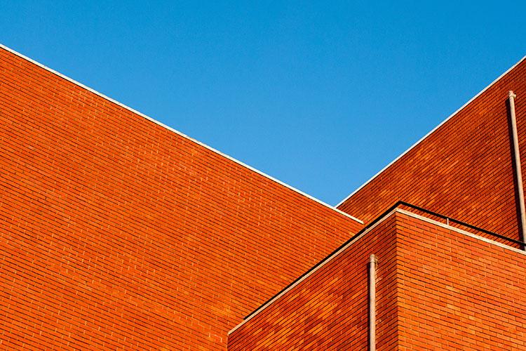 Br24 Blog Visuelle Trends 2020: Trend - Colour Flash; Teil einer orangefarbenen Steinmauer vor blauem Himmel