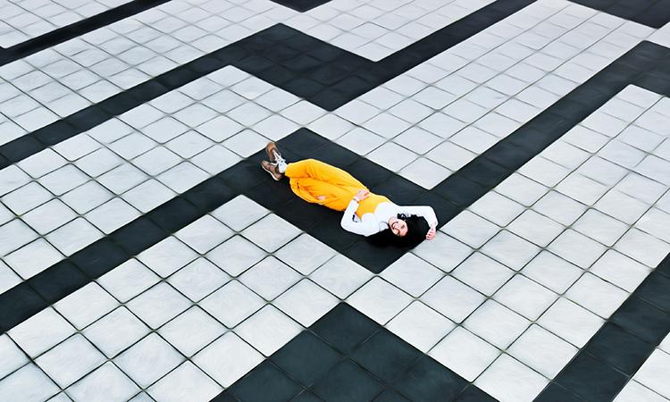 Br24 Blog Visuelle Trends 2021 Produktfotografie & E-Commerce: Trend Geometrie und Minimalismus, Frau in gelber Kleidung liegt auf schwarz-weiß geometrisch gemustertem Boden