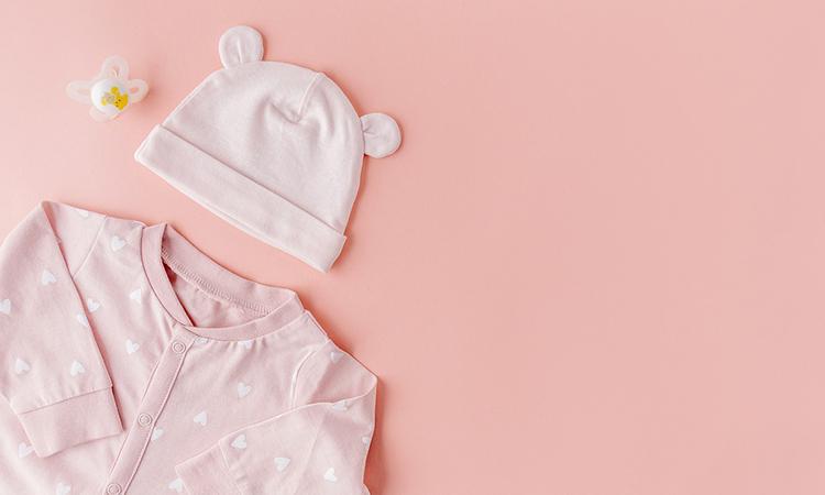 Br24 Blog Visuelle Trends 2021 Produktfotografie & E-Commerce: Trend Monochrome Farben, Draufsicht auf rosafarbene Babykleindung auf rosa Hintergrund