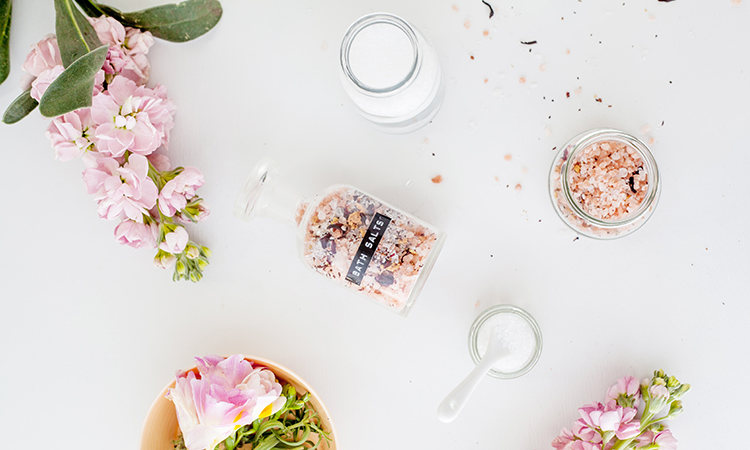 Br24 Blog Visuelle Trends 2021 Produktfotografie & E-Commerce: Trend Farben für Optimismus und Wohlbefinden, Draufsicht auf Flakon mit Badesalz umgeben von Blumen