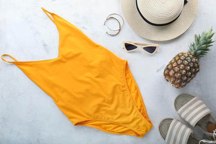 Br24 Blog image composition: Main subject - yellow swimsuit with other accessories such as hat, pineapple, sandals