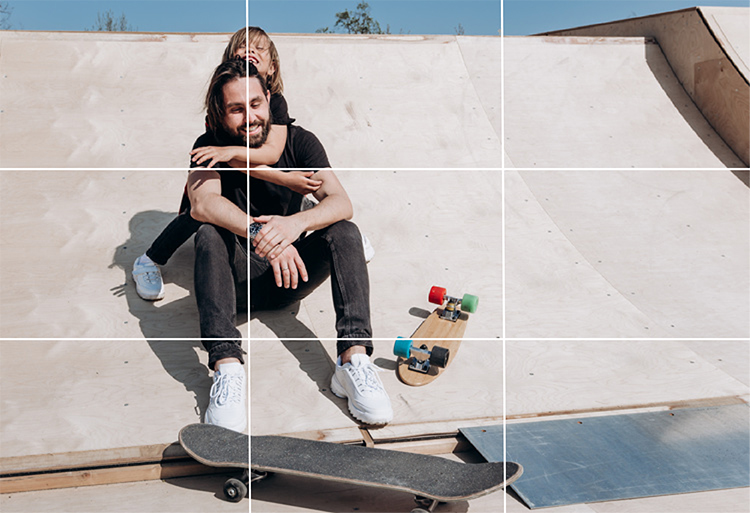 Br24 Blog Image composition: Rule of Thirds - Young man and boy sit with their skateboards at a skateboard ramp