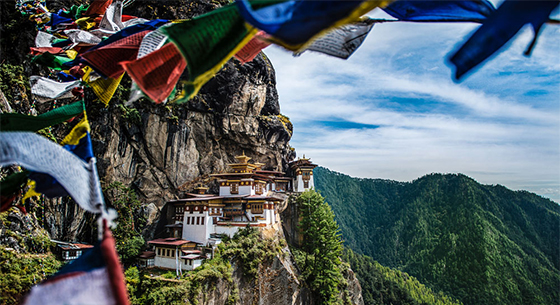 Br24 Image Retouching / Nature Photography: Tiger's nest monastery in Bhutan, photoof the monastery with mountain landscape, colourful prayer flags in the foreground