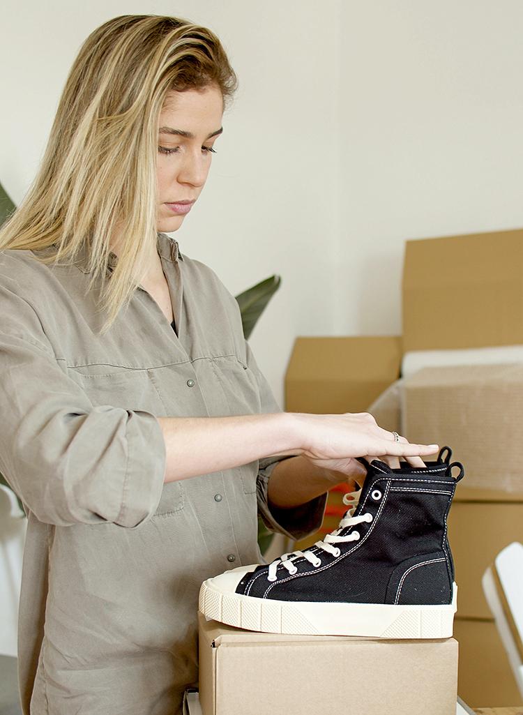 Br24 Schuhe fotografieren für Produktbilder: Frau bereitet ein Paar Turnschuhe für ein Fotoshooting vor