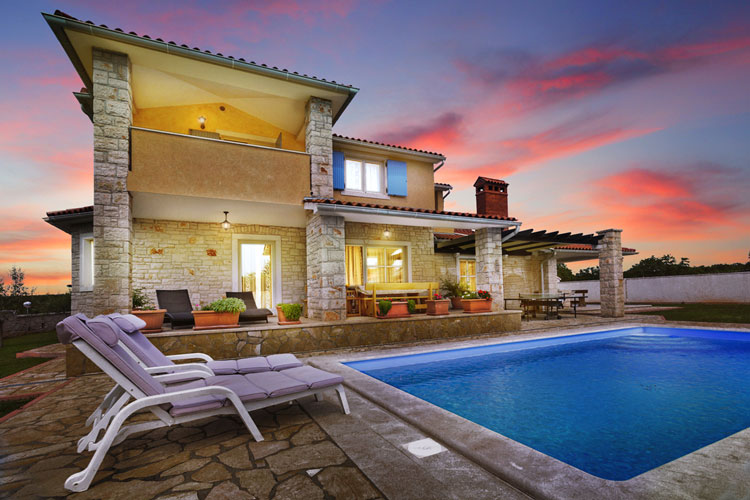 Real Estate: Exterior view of a house with a pool in an atmospheric evening mood after sky change through image editing