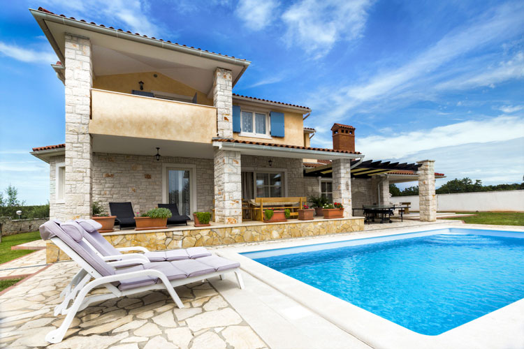 Real Estate: Exterior view of a house with a pool in broad daylight before sky change through image editing