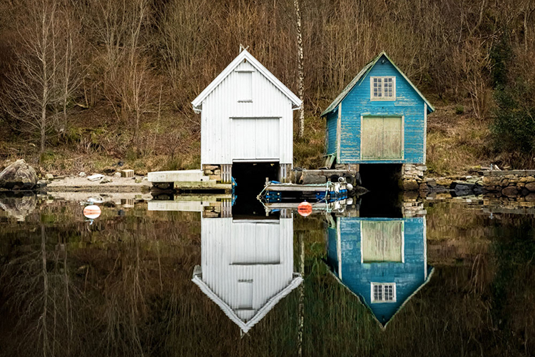 Br24 Blog Visual Trends 2018 Silence and Serenity: Two old boathouses on the edge of a lake and their reflections in the water