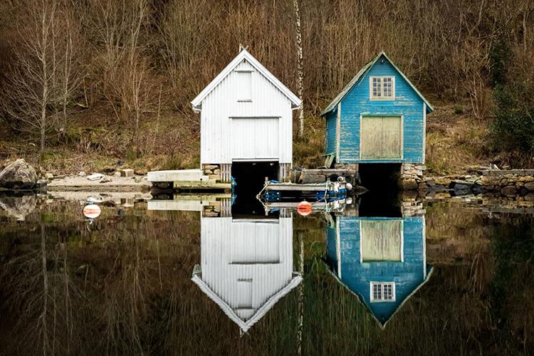 Br24 Blog Visuelle Trends 2018 Stille und Gelassenheit: Zwei alte Bootshäuser am Rand eines Sees und ihre Reflexionen im Wasser