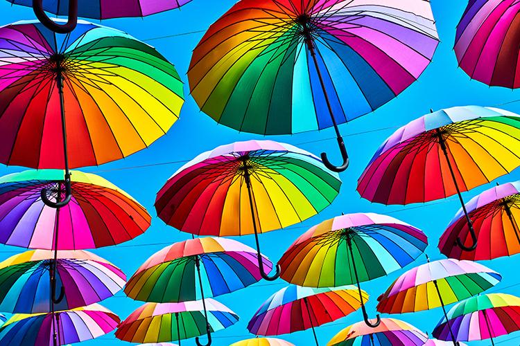 Blog Visuelle Trends 2018 Farbenfroh und auffällig: Regenbogenfarbige Regenschirme mit blauem Himmel als Hintergrund