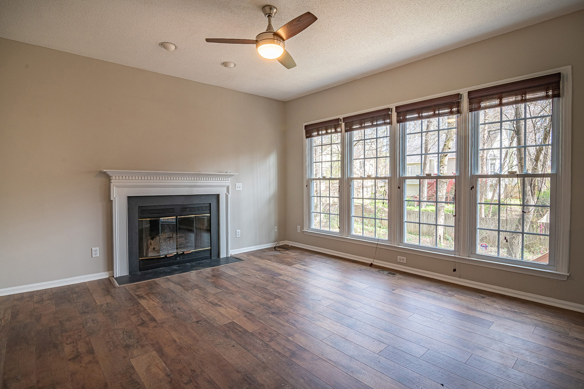 Real Estate: Empty room with big windows and a fireplace before virtual staging
