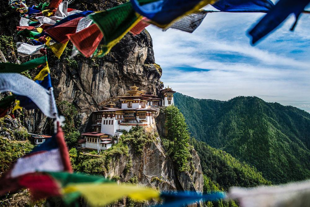 Br24 Naturfotografie, Bildretusche: Tigernest Kloster in Bhutan, Foto des Klosters mit Berglandschaft, bunte Gebetsfahnen im Vordergrund