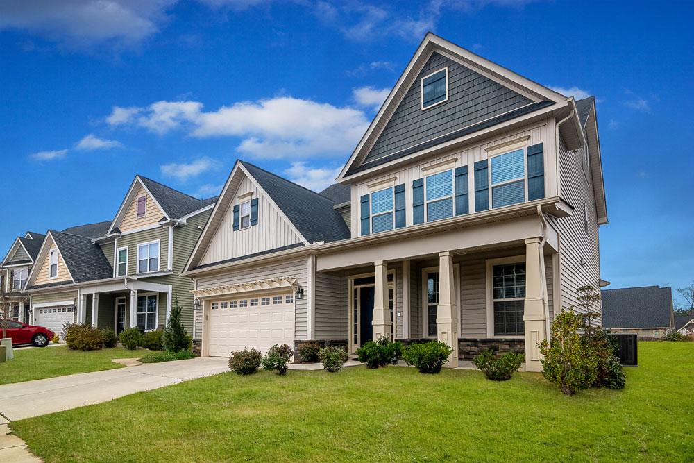 Br24 Immobilien, Retusche: Außenansicht einer Häuserreihe, blauer Himmel und grüner Rasen, nach der Retusche