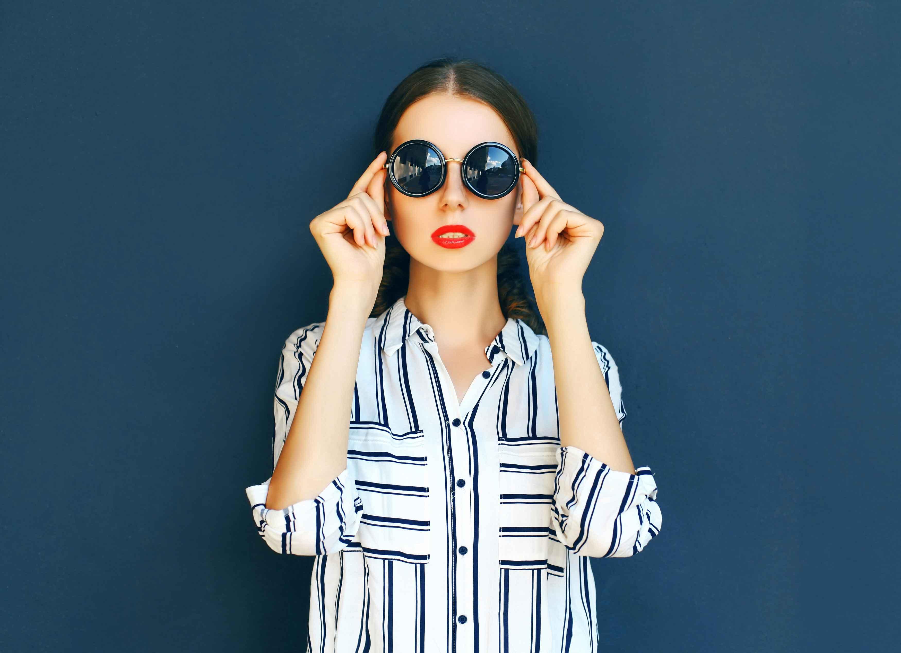 Br24 Composing: cool woman with dark sunglasses, blue stripes shirt in front of dark background before composing / Br24 Composing: coole Frau mit dunkler Sonnenbrille, gestreiftem Shirt vor dunklem Hintergrund bevor Composing