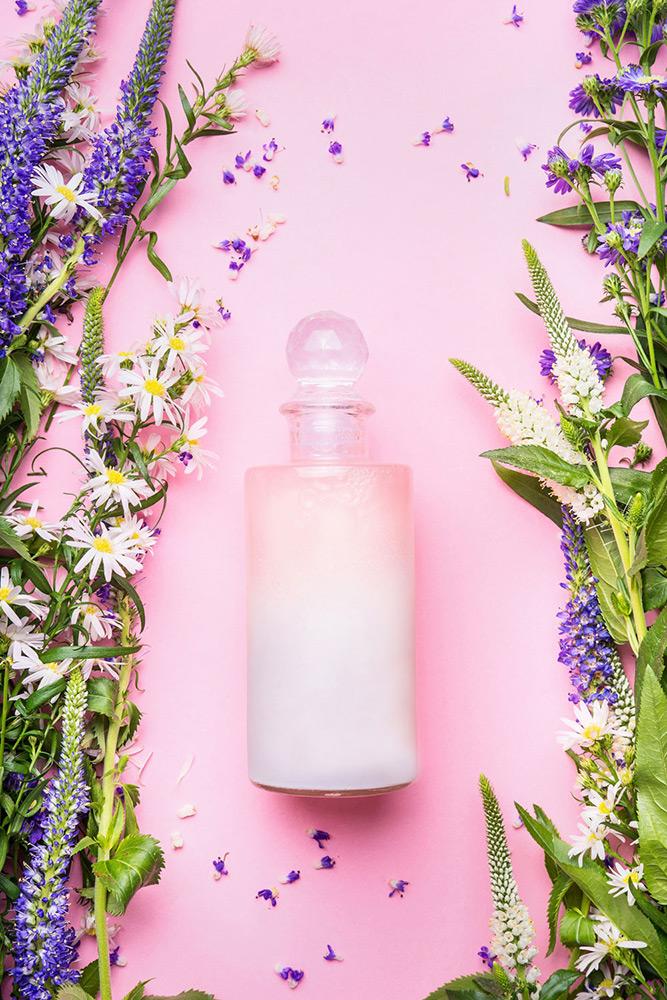 Br24 Werbung & Marketing, Bildbearbeitung, Farbkorrektur: Kosmetikflasche gefüllt mit weißer Creme auf einem hellem rosa Hintergrund, umrahmt von einem Blumenarrangement