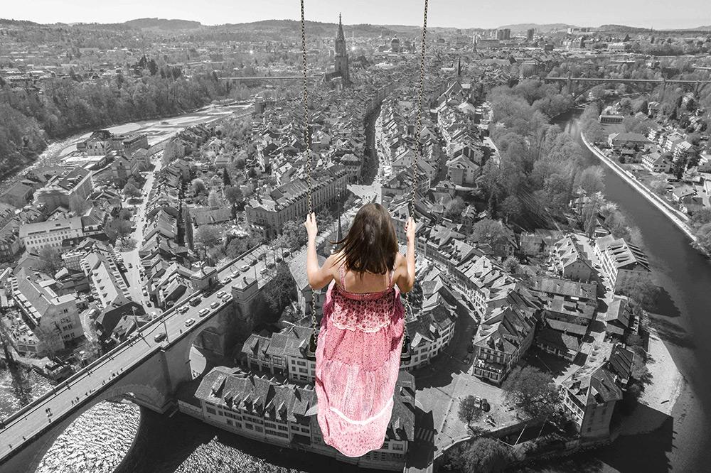 Br24 Composing: junges Mädchen im Blumenkleid auf einer Schaukel hoch über einer schwarz-weißen Stadtszzene
