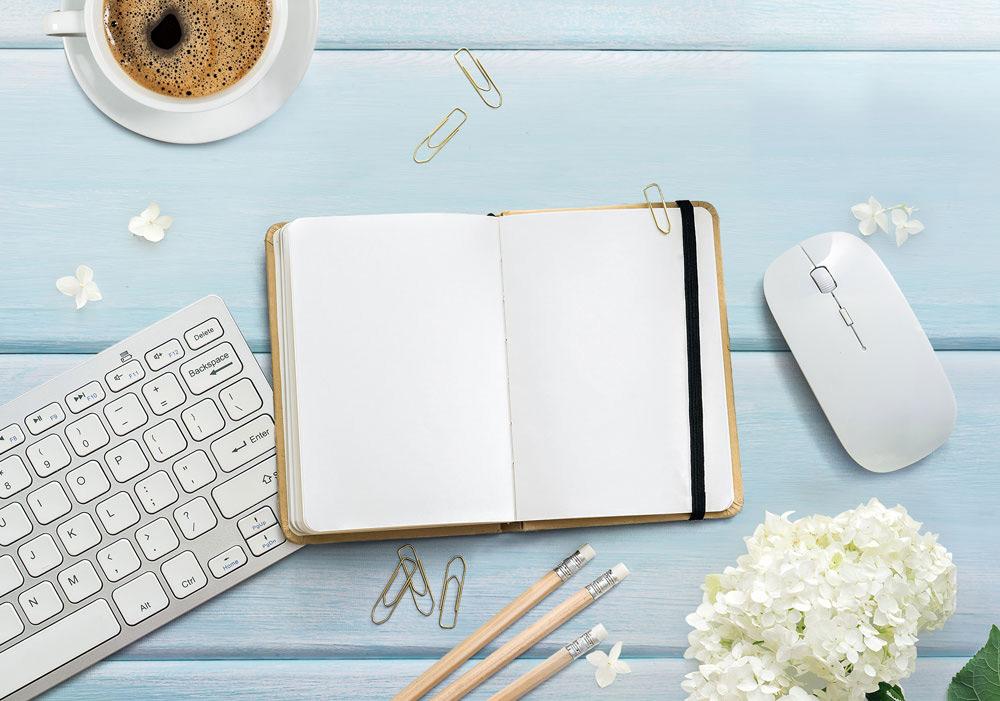 Br24 Composing: Werbung, weisser Holztisch mit Tastatur, Blumen, Notizbuch, Kaffee und Bleistiften nach dem Composing
