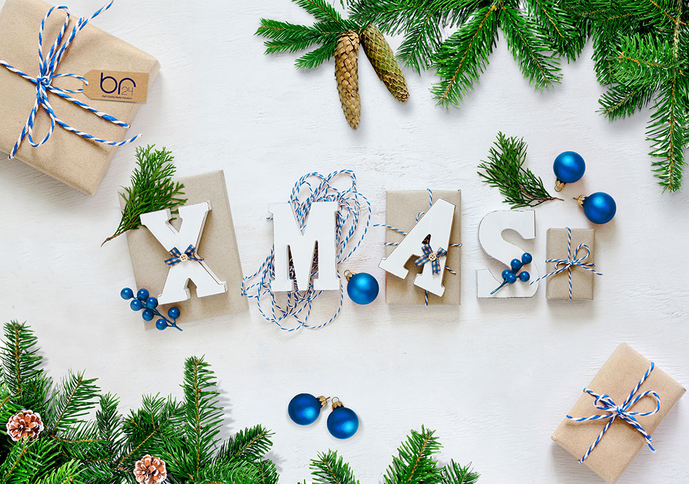 Br24 Composing: Gifts with the Letters XMAS surrounded by fir branches and glitter ball