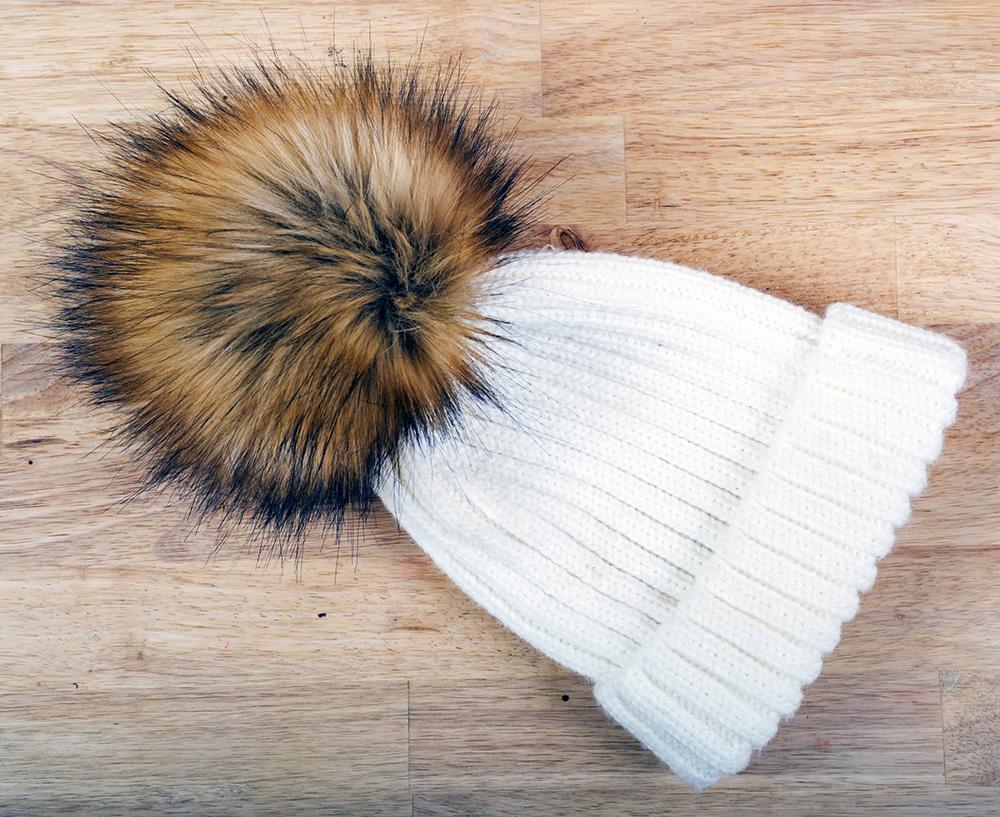 Br24 E-Commerce: Alphamasking: getrickte Mütze mit Fellbommel auf Holzhintergrund, bevor Alphamaske