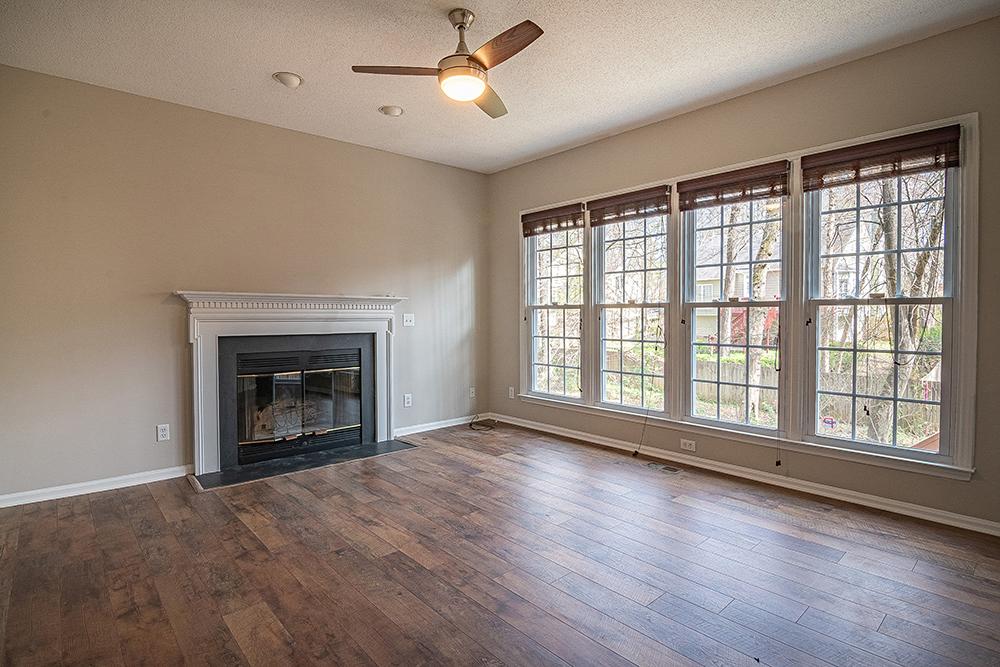 Br24 Immobilien, Virtual Staging: leeres Wohnzimmer mit Kamin und großen Fenstern, vor Virtual Staging