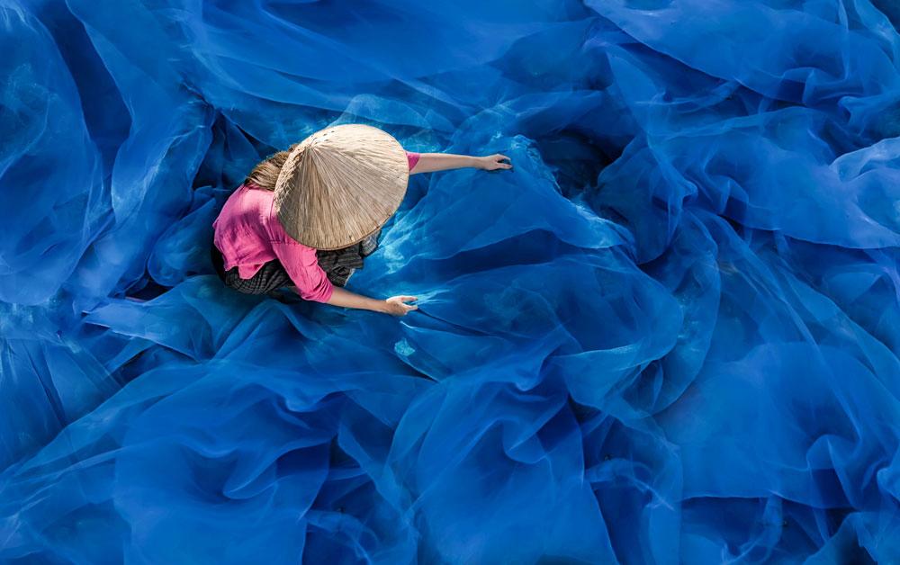 Br24 Farbkorrektur, Werbung: Frau mit Strohhut inmitten leuchtend blauem Fischnetz nach Farbkorrektur