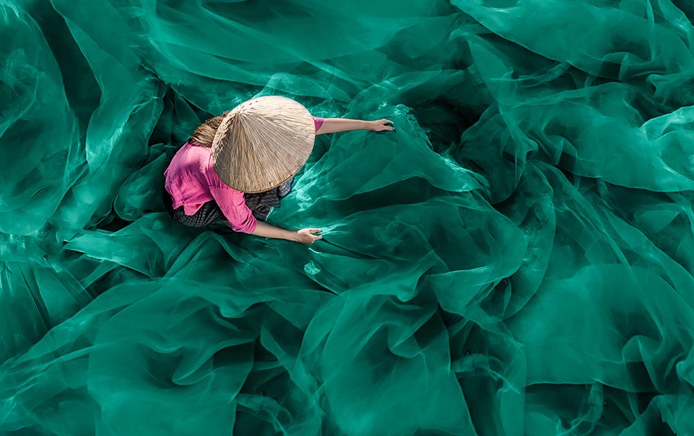 Br24 Farbkorrektur, Werbung: Frau mit Strohhut inmitten leuchtend grünem Fischnetz vor Farbkorrektur